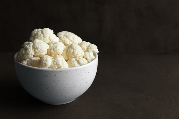 Raw cauliflower slices in a light bowl on a dark background with copy space.