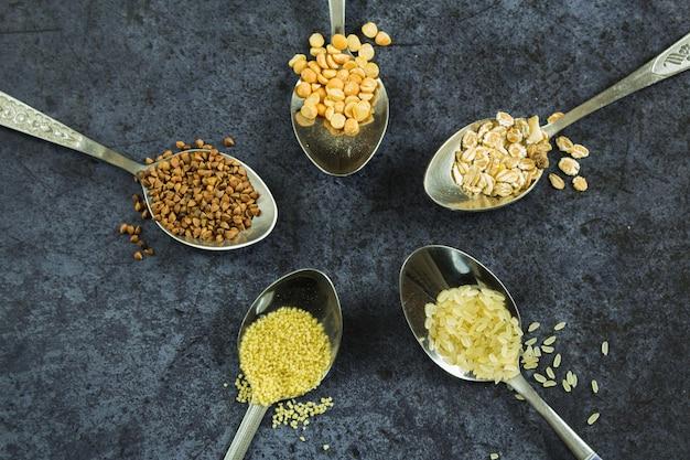 暗い背景のクローズアップ上面図のスプーンで生の穀物