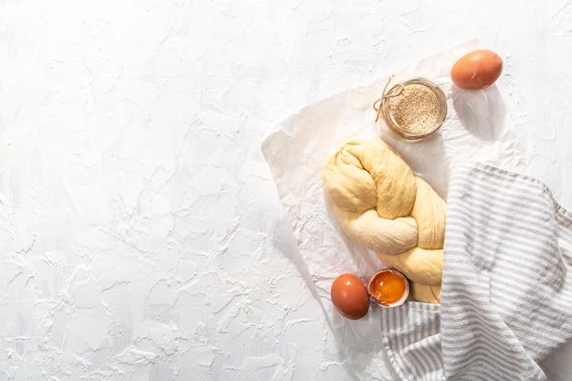 Сырой хлеб халы на бумагу для выпечки