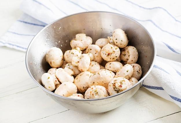 Сырые грибы шампиньоны в миске на белом деревенском фоне, подготовленные для выпечки