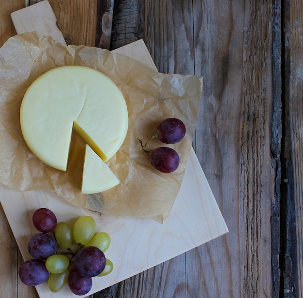 Raw cheese platter on rustic background, top view