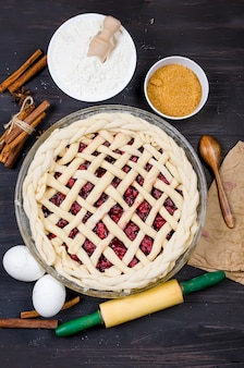 Raw cherry pie in a glass round form and ingredients