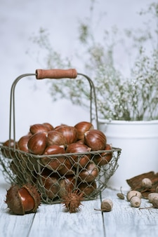 Raw chestnuts on a wooden background in an iron basket