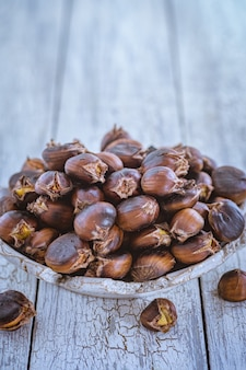 Raw chestnuts on a wooden background in an iron bowl