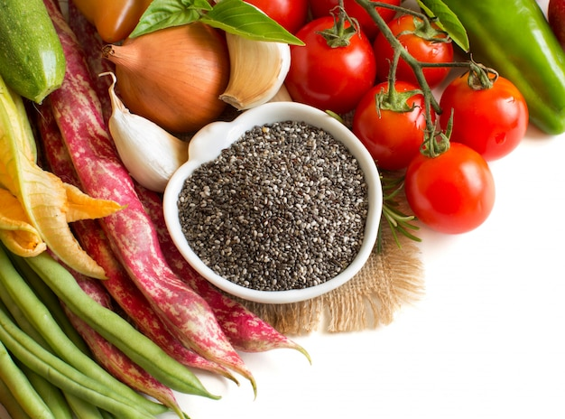 ボウルと白で隔離される野菜の生チア種子をクローズアップ