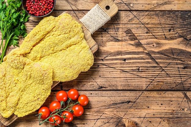 生の鶏肉のパン粉をまぶしたワイナーシュニッツェル。木製の背景。上面図。スペースをコピーします。