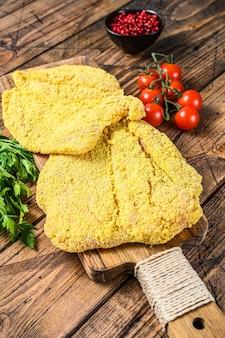 Сырая курица вайнерский шницель в панировке. деревянный фон. вид сверху.