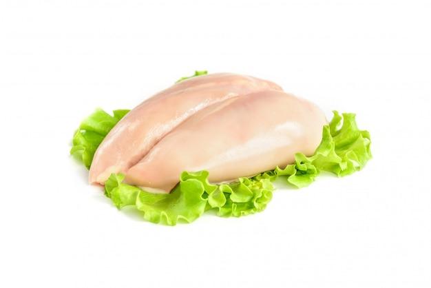 Сырая куриная грудка и зеленый салат, изолированные на белом фоне.