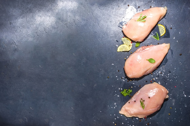 Raw chicken breast filet on dark concrete background with spices and herbs for cooking, top view copy space