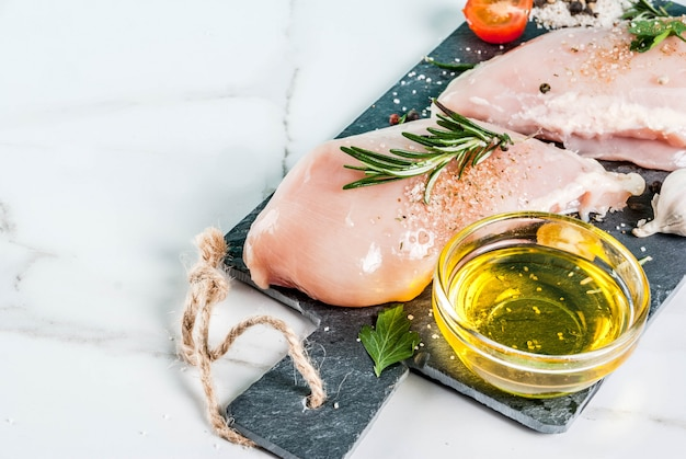 Raw chicken breast filet meat with spices and olive oil