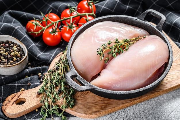 허브와 향신료와 함께 냄비에 생 닭 가슴살 등심. 흰 배경. 평면도.