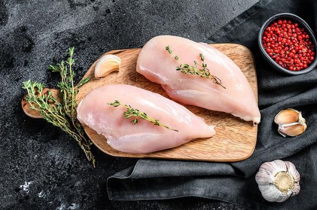 ハーブとスパイスをチョッピングボードに生の鶏の胸肉の切り身。黒の背景。上面図