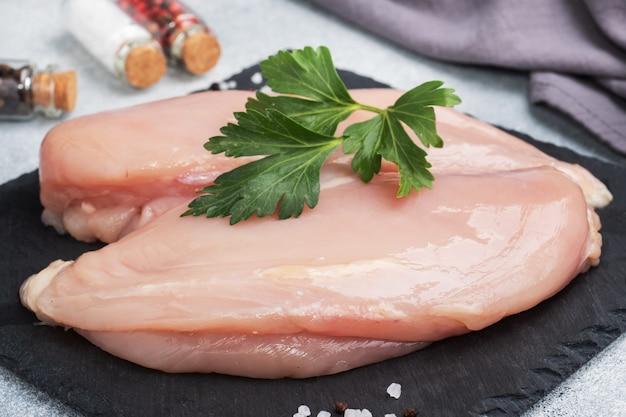 생 닭 가슴살 필레, 검은 스탠드에 생 닭고기, 회색.