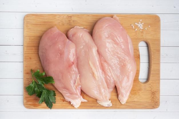 생 닭 가슴살 등심, 도마에 생 닭 고기. 하얀,