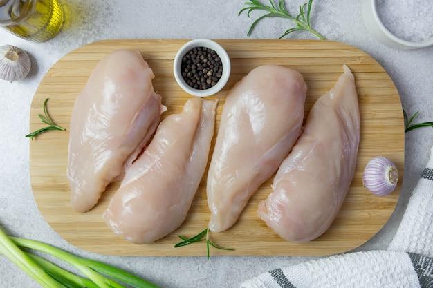 Сырое филе куриной грудки со специями и травами на светло-сером фоне.