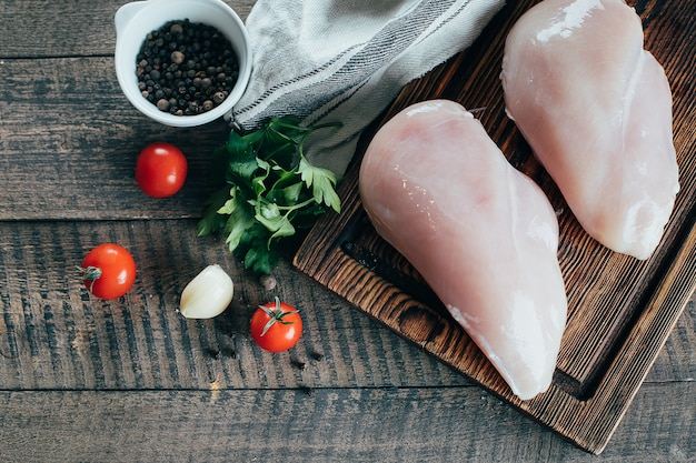 Raw chicken breast fillets and ingredients for dinner on wooden board on table background