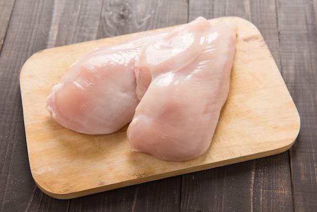 木製の背景に生の鶏の胸肉の切り身