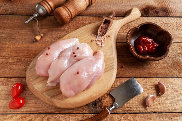 素朴な踏み越し段にトマト、ケチャップ、スパイスを添えた生の鶏胸肉の切り身