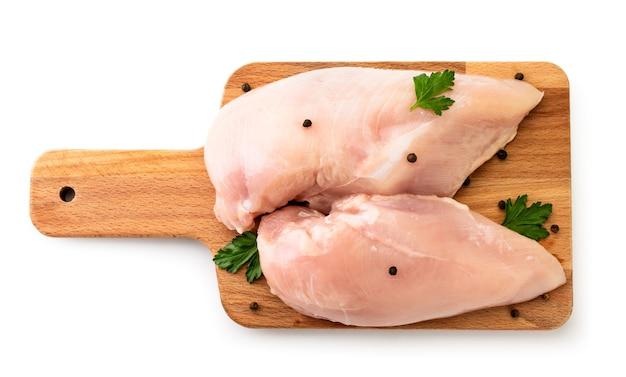 Сырая куриная грудка на разделочной доске с перцем и петрушкой вид сверху.