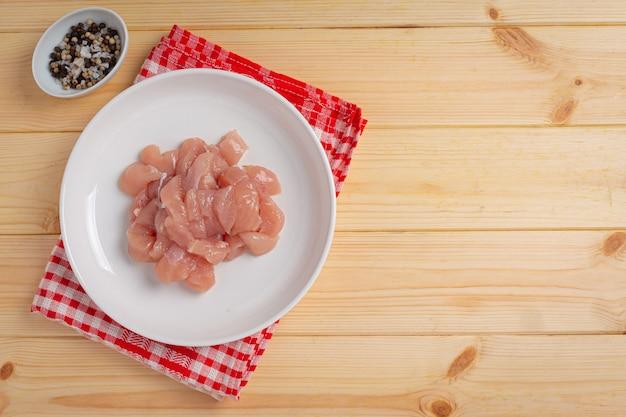 Сырая куриная грудка на деревянной поверхности.