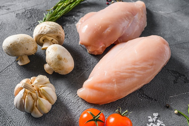 Сырая куриная грудка со свежим розмарином, чесноком, перцем и грибами