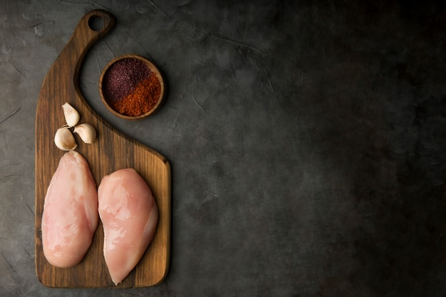 Raw chicken breast with garlic and spices