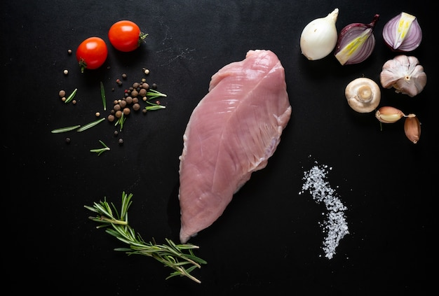 Raw chicken breast with herbs, spices, garlic cloves, tomato and onion as a flat lay still life on black