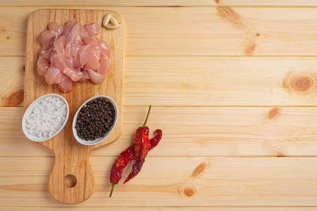 Petto di pollo crudo sulla superficie in legno.