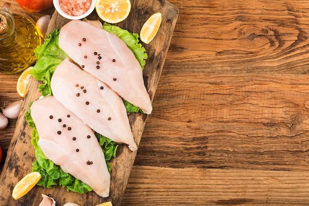 木製のまな板に生の鶏の胸肉とスパイス