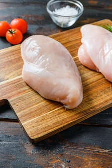 Сырые куриные грудки и специи на деревянной разделочной доске