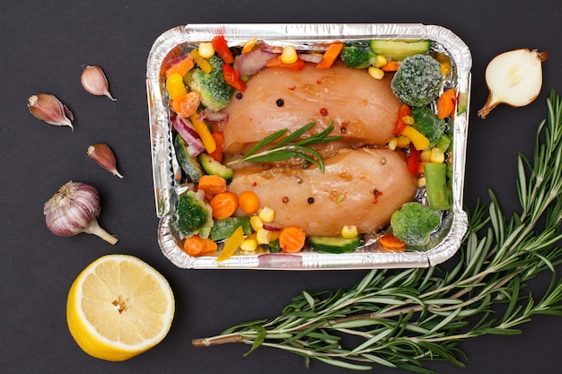 Сырые куриные грудки или филе в металлическом контейнере с ингредиентами.