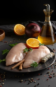 Raw chicken breasts prepared for cooking with ingredients,vertical view