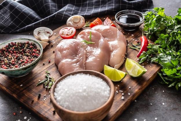 Сырые куриные грудки, соевый соус, грибы, помидоры, лимон, перец чили, перец, соль и петрушка на деревенской деревянной разделочной доске и черном фоне.