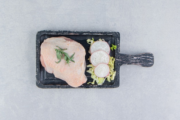 Raw chicken breasts and spices on the board, on the white surface