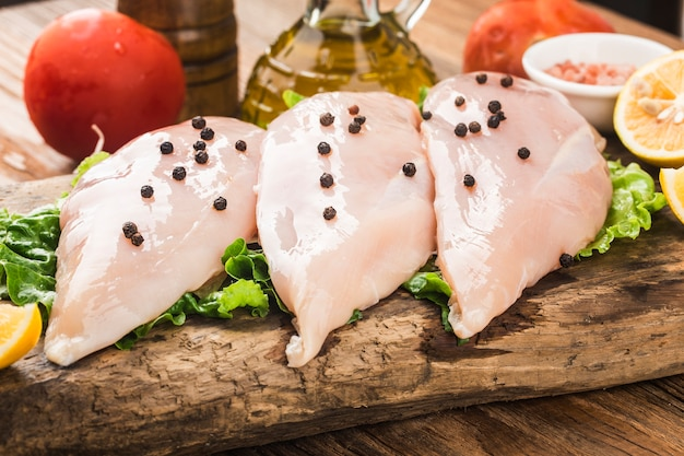 Raw chicken breasts and spices on wooden cutting board