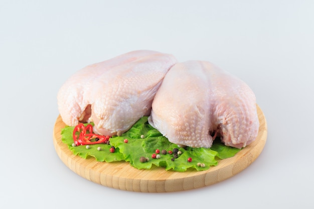 Raw chicken breasts on white