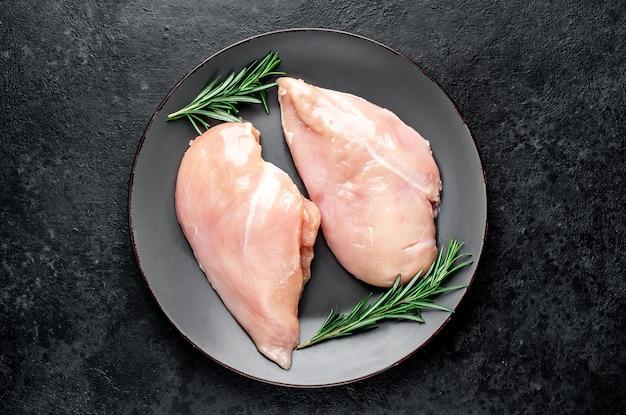 Сырые куриные грудки с ингредиентами на каменном столе