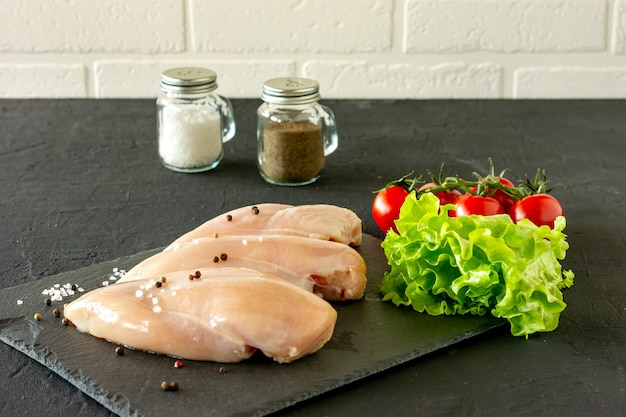 Сырые куриные грудки с петрушкой и помидорами готовы к приготовлению. диетическое питание.