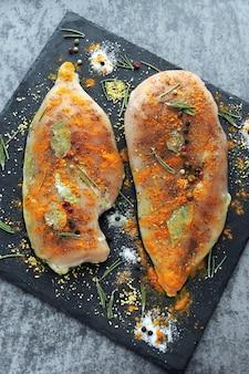 石板にスパイスと海塩を添えた生の鶏の胸肉