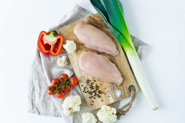 Raw chicken breasts on a wooden chopping board.