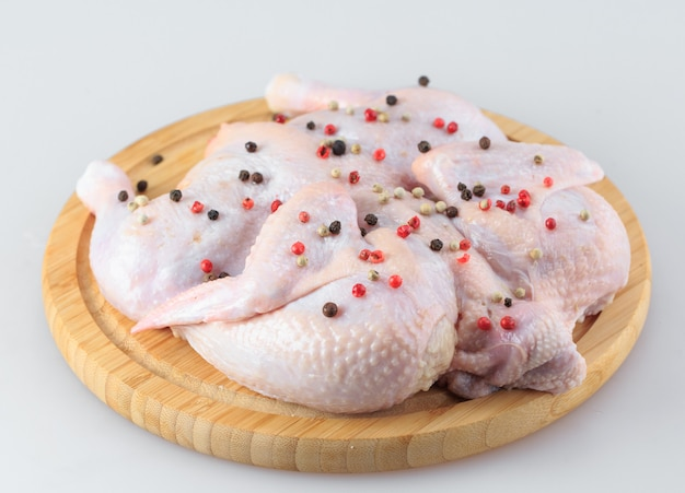 Raw chicken carcass on the cutting board isolated on white