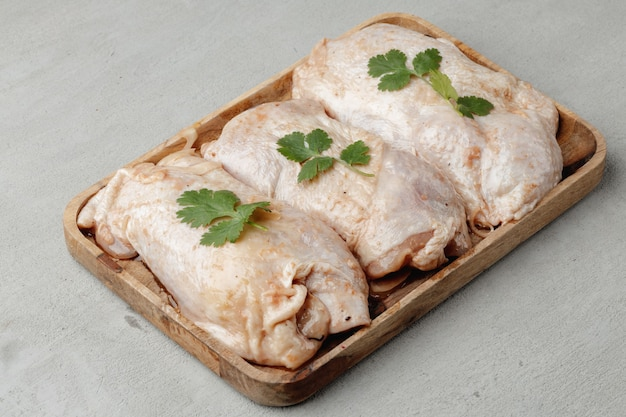 나무 접시에 원시 닭 시체를 닫습니다.