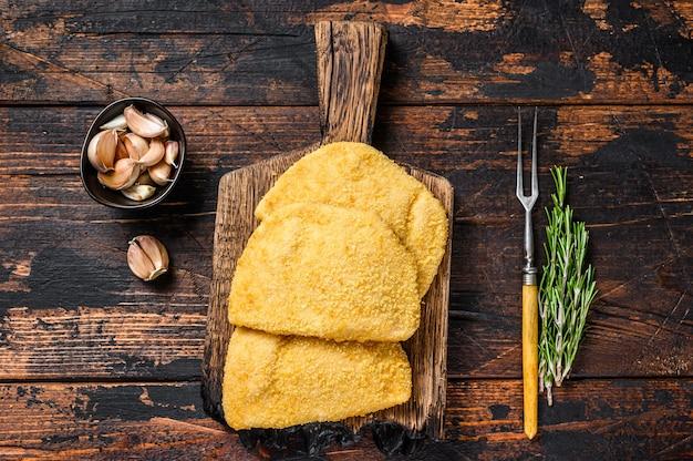 木製のテーブルの上の木の板にパン粉と生のチキンコルドンブルーミートカツレツ。上面図。