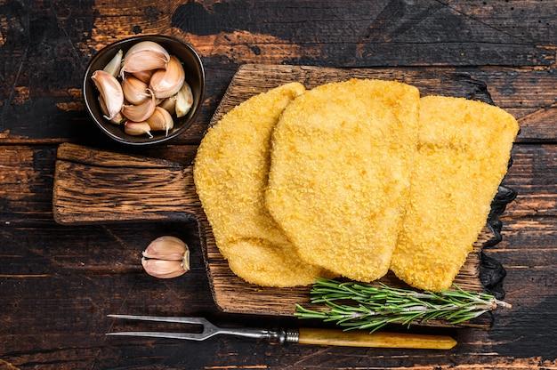 Сырые куриные котлеты из мяса кордон блю с панировочными сухарями на деревянной доске