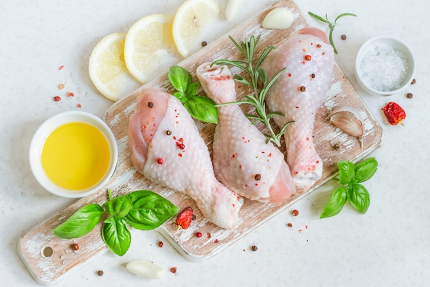 Raw chicken drumstick on a cutting board with spices prepared fo