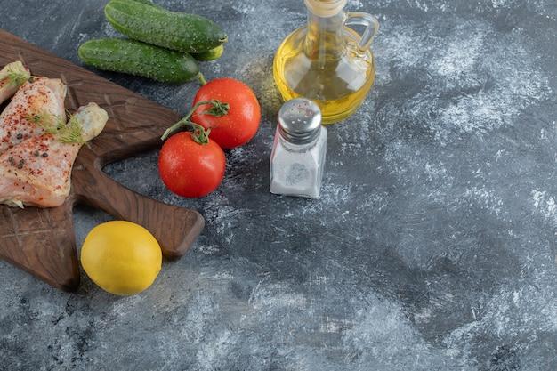 Coscia di pollo crudo e verdure fresche.