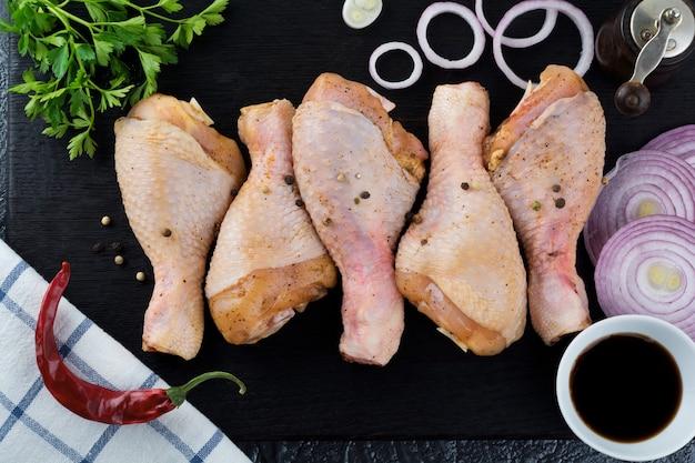 Сырая куриная голень в маринаде с перцем, соевым соусом, петрушкой и луком на черной деревянной подставке. выборочный фокус. вид сверху.