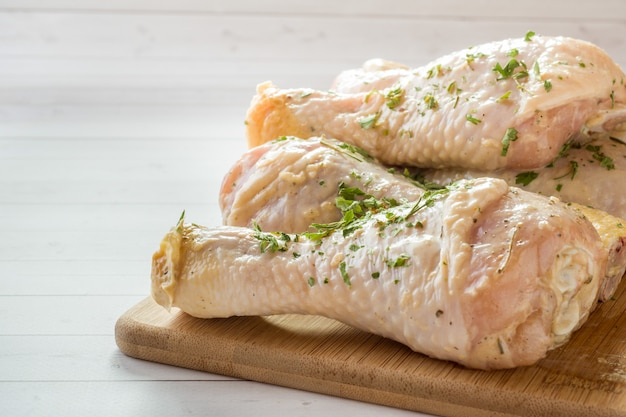 Raw chicken drumstick in marinade with sauce, pepper and greens