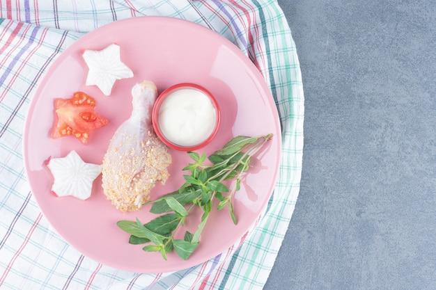 Coscia di pollo crudo e maionese sul piatto rosa.