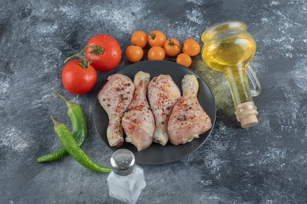 Сырая куриная голень на черной тарелке со свежими овощами и специями.